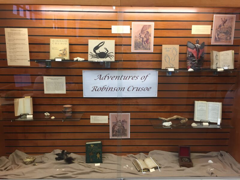 """A display of various books and items related to the novel """"Adventures of Robinson Crusoe""""."""