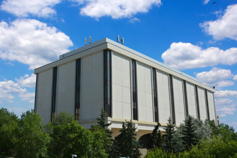 A photo taken from ground level looking up at the Archer Library. Trees are in the foreground and the sky is blue with white clouds.