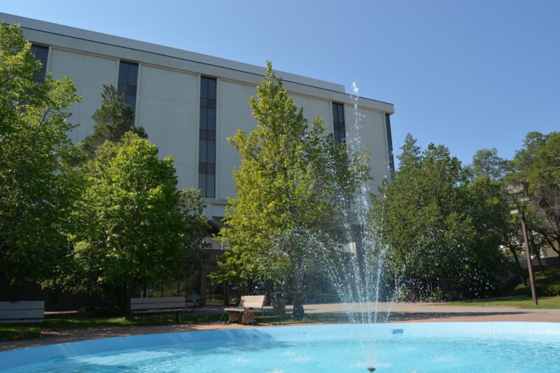 A fountain in front of the Archer Library. There are benches and trees surrounding the fountain.