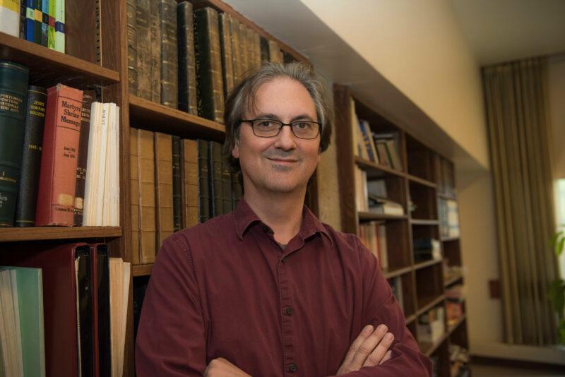 Headshot of Dwayne Meisner standing in front of a bookshelf.